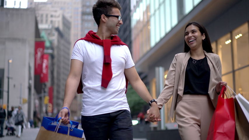 Latino American couple in love discussing something while walking in shopping district with paper bags in hands and smiling during conversation, man and woman dressed in stylish apparel strolling | Shutterstock HD Video #1031912423