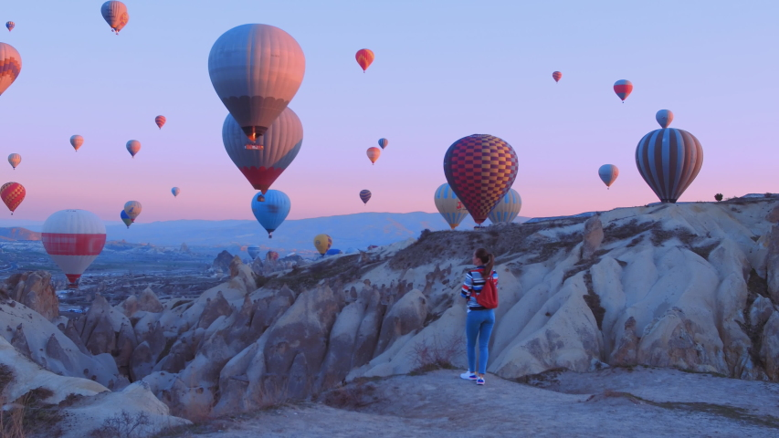 Female traveler with backpack looking to the air baloons. sporty girl and a lot of hot air balloons. The feeling of complete freedom, achievement, achievement, happiness