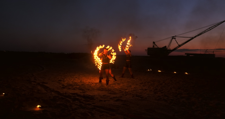 Fire show. A group of professional artists performs a variety of fire facilities. Boys and girls performed dances with fire in the night on the street in the Park. Royalty-Free Stock Footage #1031919995