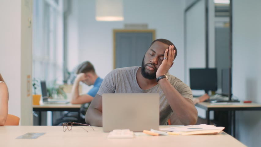 Sleepy man sleeping at workplace. Tired guy almost falling down from chair. Boring man trying to work at coworking. Slipping man rubbing eyes in business office. | Shutterstock HD Video #1031923739