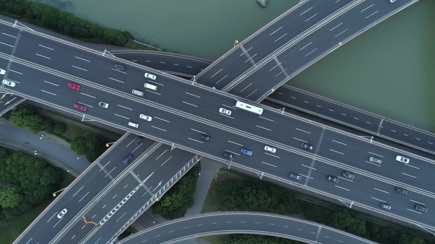 Aerial drone view of highway multi-level junction road with moving cars at sunset. Cars are moving on a multi-level road junction The concept of the urban. Suzhou city, China. Royalty-Free Stock Footage #1031950844