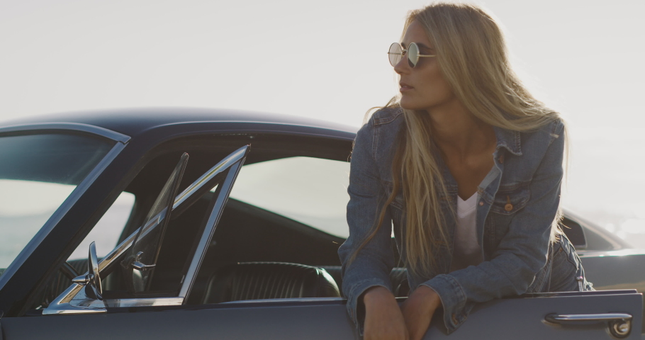 Attractive woman wearing a denim jacket and sunglasses leaning on a classic vintage sports car, edgy vintage muscle car
