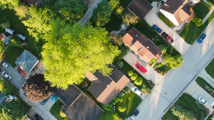 Aerial view of residential houses at summer. Establishing shot of American neighborhood, suburb, house.  Real estate, drone shots, sunrise, sunlight, from above