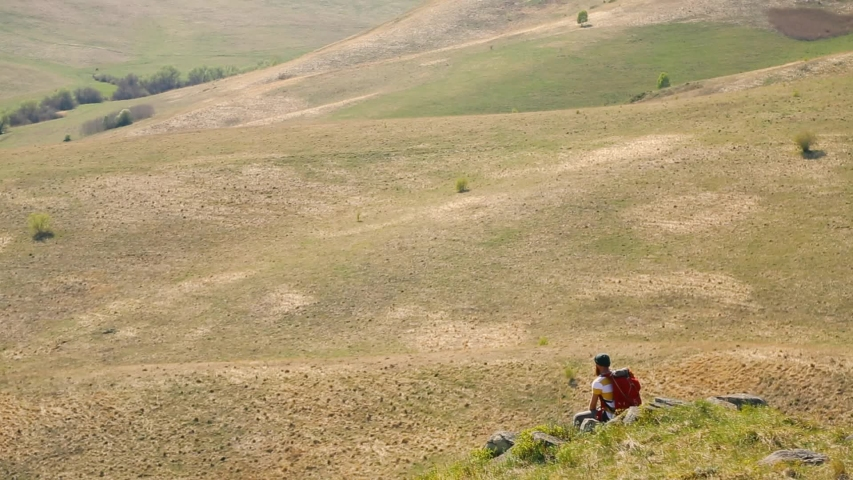 Man with a beard mustache with a red backpack parachute green hat striped white yellow T-shirt jeans, sits on the stones in the summer and looks around. tattoo on the arm. Caucasian | Shutterstock HD Video #1031953649
