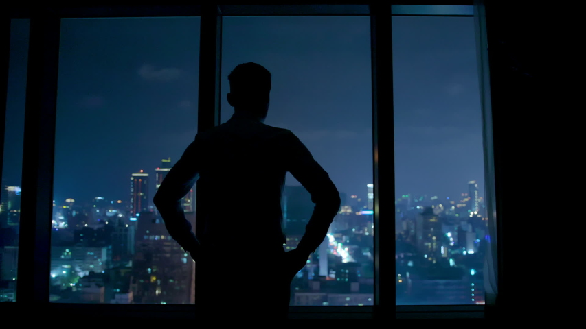 silhouette of upset businessman watching through the window at night #1031954300