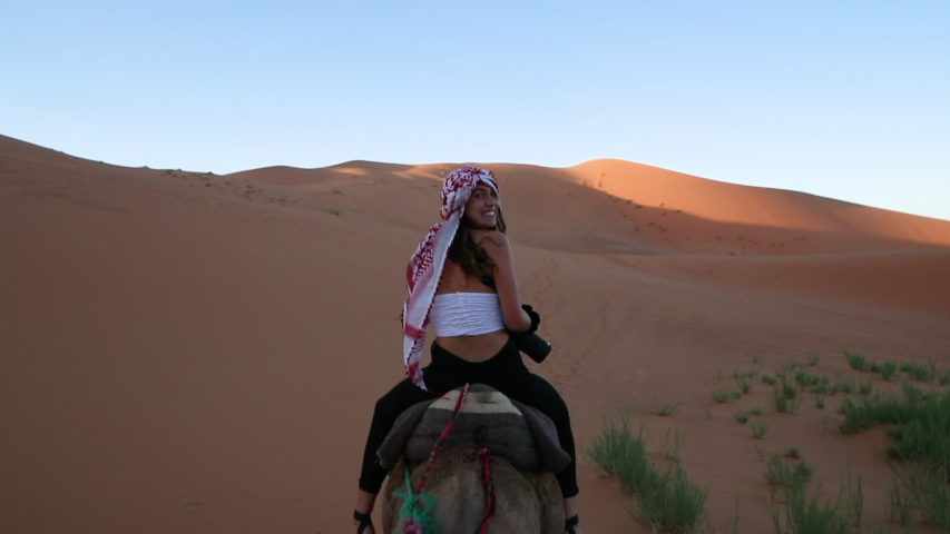 Women riding a Camel, looking back and smiling towards the Camera.