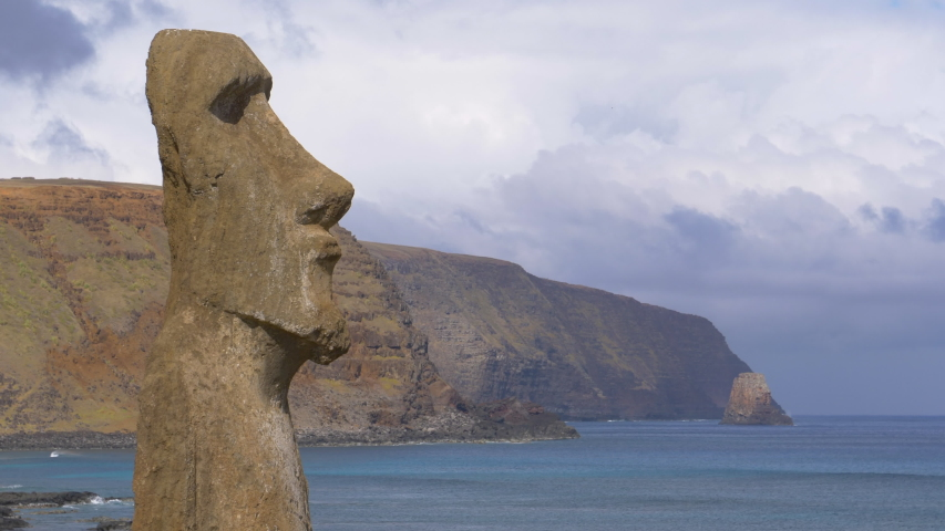 DRONE, COPY SPACE: Large volcanic sculpture with human features faces the deep blue ocean. Breathtaking view of a large mysterious moai sculpture on Easter Island. Beautiful traditional monument.
