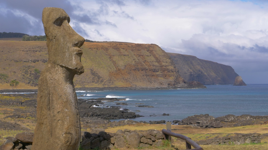 AERIAL, COPY SPACE: Spectacular view of a towering moai sculpture on a remote exotic island in Chile. Breathtaking aerial shot of the deep blue ocean behind a large monolithic statue with a human face