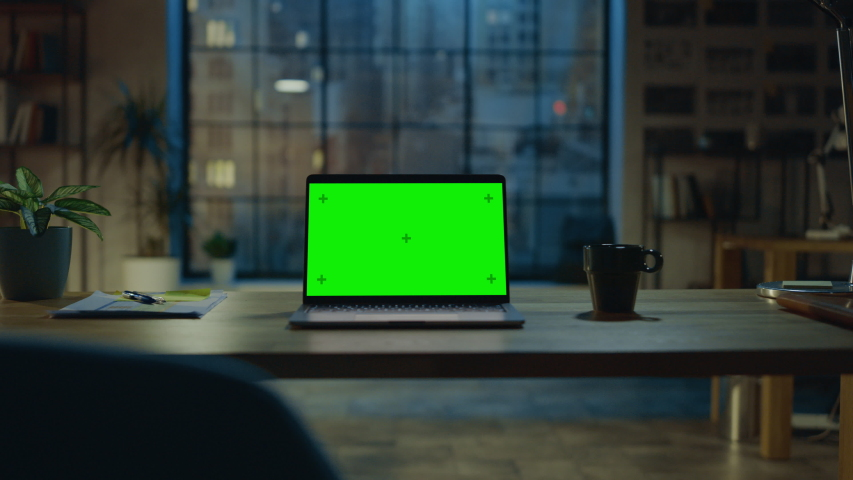 Mock-up Green Screen Laptop Standing on the Desk in the Modern Creative Office. In the Background Warm Evening Lighting and Open Space Studio with City Window View. Zoom out Shot