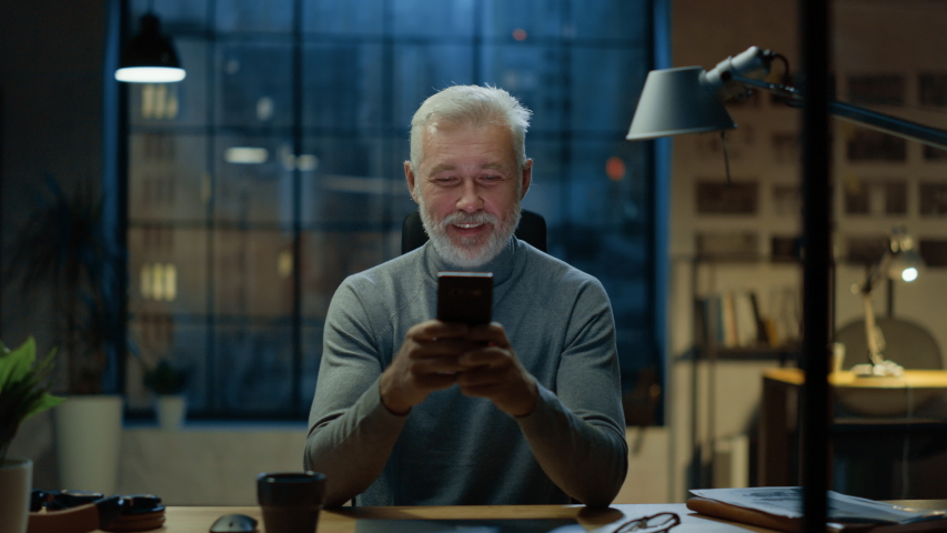 Portrait of the Handsome and Successful Middle Aged Bearded Businessman Uses Smartphone while Sitting at His Desk, He Laughs and Smiles at Something Funny. Working from Cozy Home Office / Studio Royalty-Free Stock Footage #1031975792