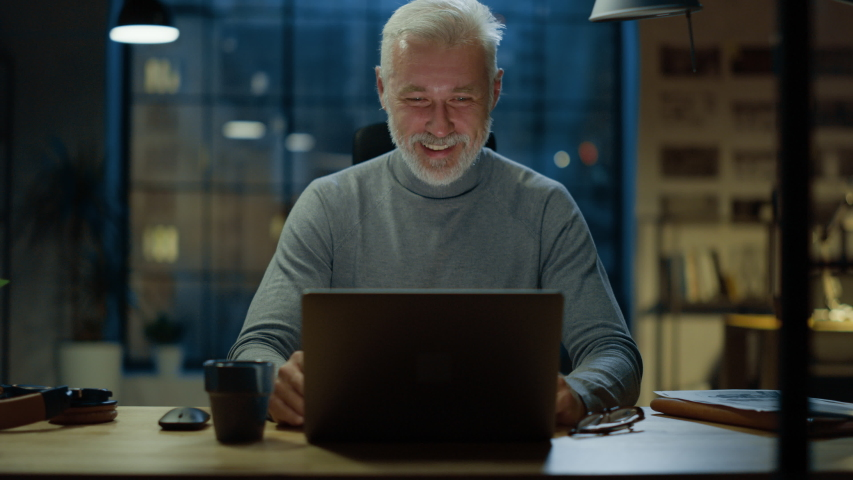 Portrait of the Handsome and Successful Middle Aged Bearded Businessman Working at His Desk Using Laptop Computer, He Laughs and Smiles at Something Funny. Working from Cozy Home Office / Studio Royalty-Free Stock Footage #1031975795