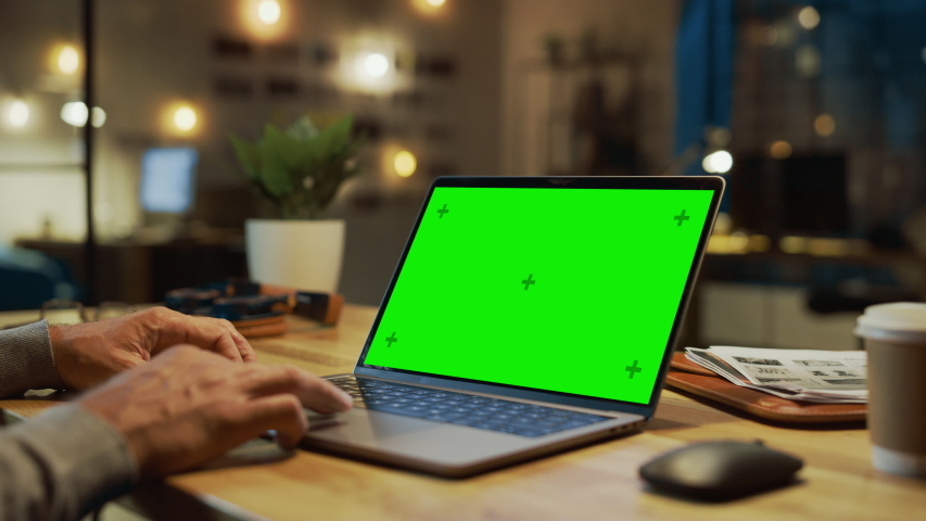 Close-up On the Hands of the Male Specialist Works on a Laptop Computer with Mock-up Green Screen. In the Background Evening in the Stylish Studio Office | Shutterstock HD Video #1031975822