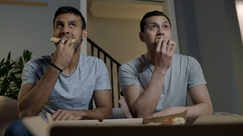 Low angle of two male friends sitting on a sofa at home eating takeaway pizza watching tv | Shutterstock HD Video #1031979827