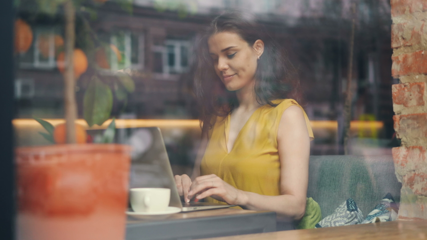 Young woman freelance is working with laptop in cafe typing smiling sitting at table alone with portable computer. People and modern technology concept. Royalty-Free Stock Footage #1031981765