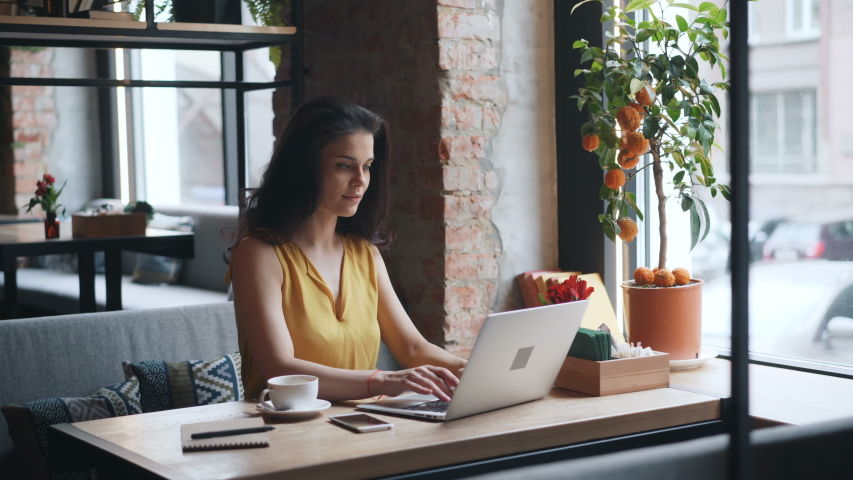 Young woman is working with laptop computer in cafe typing looking at screen smiling enjoying remote work. Happy youth and gadgets concept. | Shutterstock HD Video #1031981864