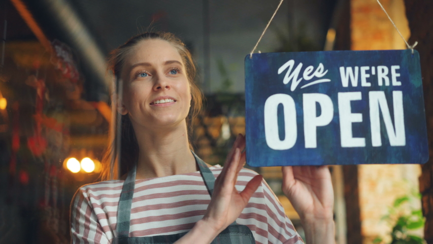 Happy cafe manager girl changing closed to open sign on window smiling looking outside waiting for clients. Small business, people and start-up concept. | Shutterstock HD Video #1031988401