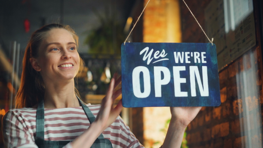Young woman in apron opening cafe in morning hanging we are open sign on front door smiling waiting for customers. Business, youth and working hours concept.   Shutterstock HD Video #1031988422