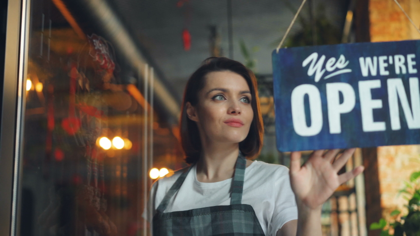 Business owner attractive woman in apron hanging we're open sign on front door smiling welcoming clients to new cafe. Business, people and youth concept. Royalty-Free Stock Footage #1031988425