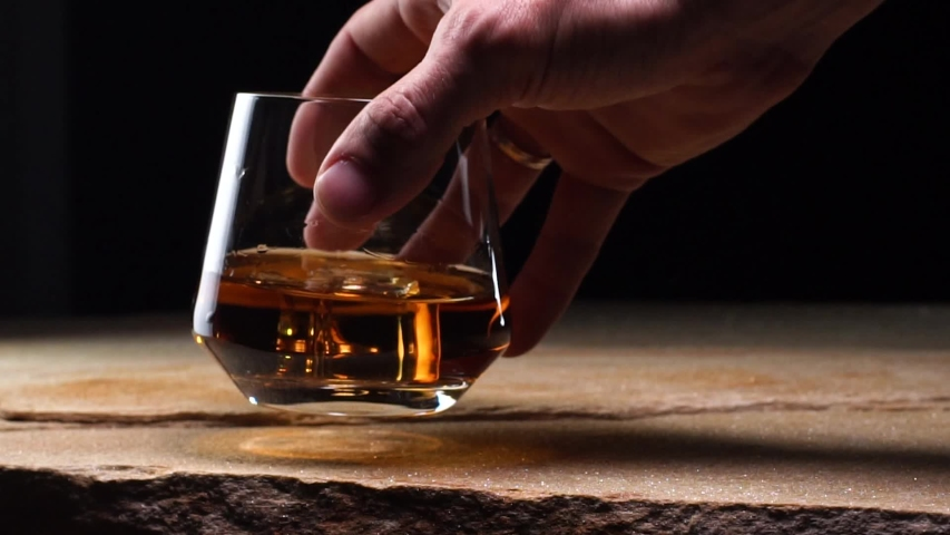 Close up Slow Motion Hand Holding A Glass Goblet With Whiskey And Ice And Swinging It Over The Stone Tabletop And Black Background. Concept Of Fine Alcoholic Drinks Alcoholism And Tasting Drinks | Shutterstock HD Video #1031991416