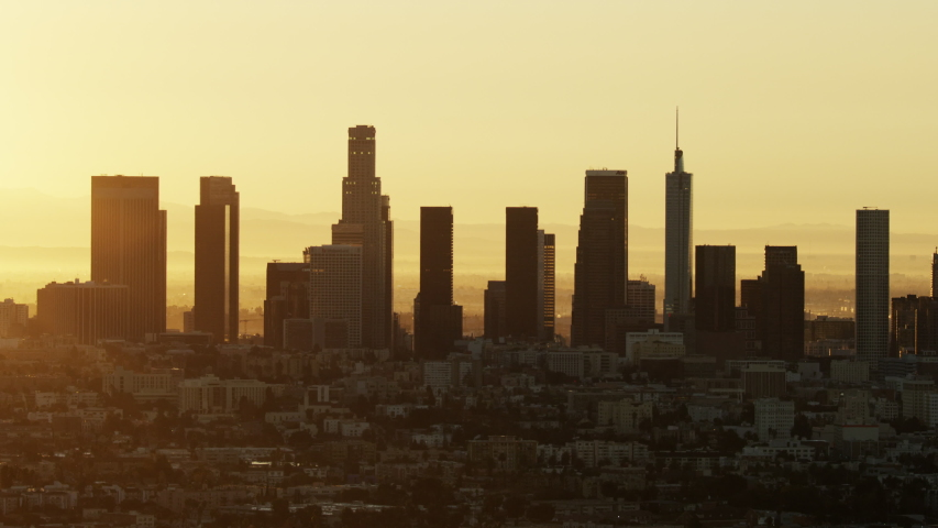 Aerial sunrise view across urban neighborhood commercial and residential buildings with city skyscrapers Los Angeles skyline California USA | Shutterstock HD Video #1032005804