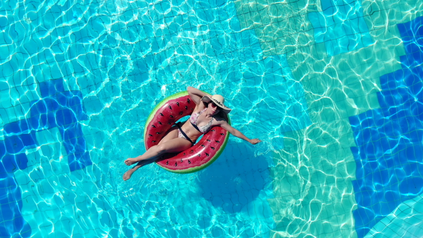 A woman is relaxing while floating in a swim ring. Summer vacation concept.