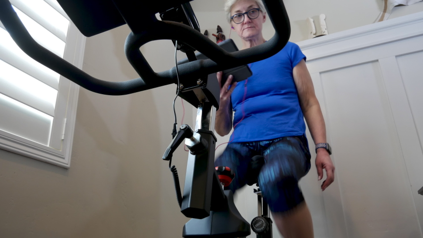 Mature woman reads her tablet while riding stationary bike - low angle looking up | Shutterstock HD Video #1032024518