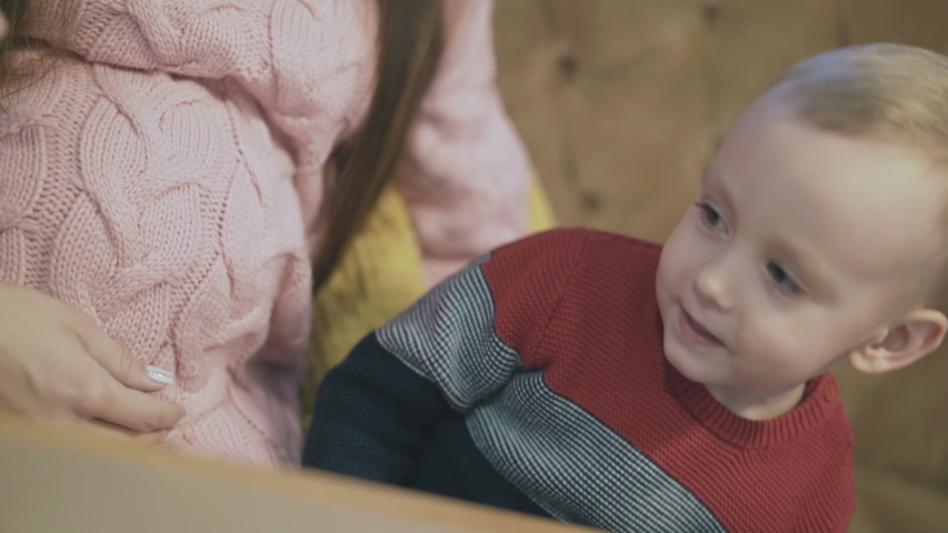 Funny kid looks at pregnant woman in pink pullover belly and touches sitting on brown sofa in cafe extreme close view