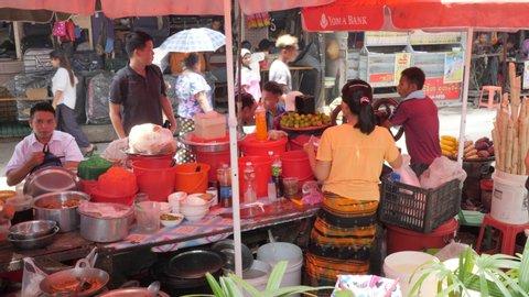 Yangon, Myanmar - 18.05.2019: Street food restaurant with people eating traditional asian food.
