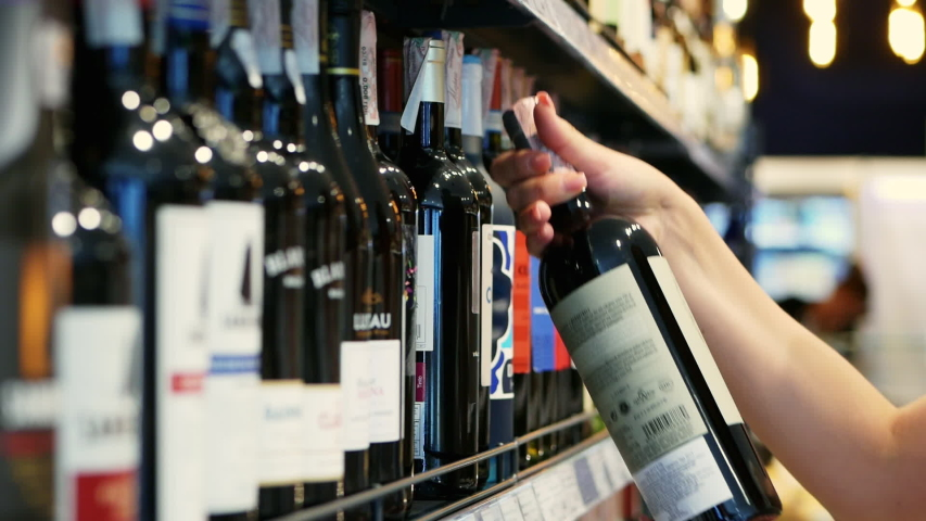 Woman chooses wine in the Supermarket, customer selects product on the shelves in the store in close-up Alcohol sale | Shutterstock HD Video #1032081818