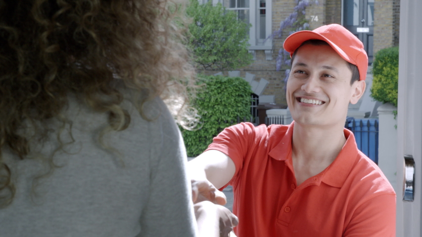 A woman opens her front door to a smiling delivery man delivering delicious takeaway food. Online ordering and delivery concept. | Shutterstock HD Video #1032095246