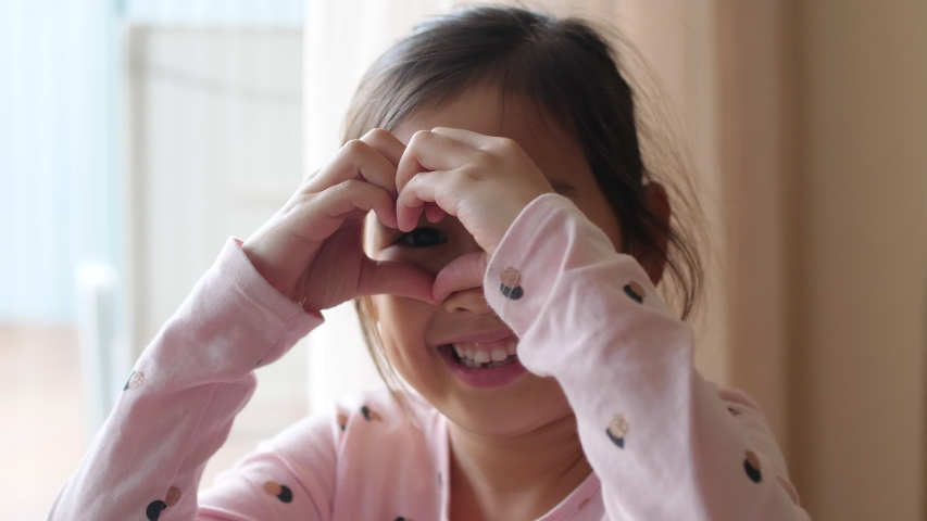 4K Slow motion of happy little mixed ethnic Asian girl making heart shape gesture with her hands over her eyes , donate, charity, care, love, heart health, mental health,  thank you concept Royalty-Free Stock Footage #1032102992