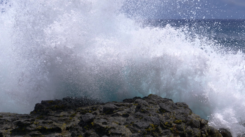CLOSE UP: Big waves crash into the black volcanic rocks on the remote shore of Easter Island. Cinematic shot of a deep blue ocean swell violently splashing over the rocky coast of an exotic island.