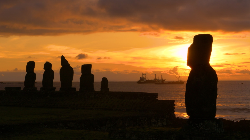 DRONE, SILHOUETTE, COPY SPACE: Golden sunset illuminates the legendary moai statues in Ahu Tahai and fishing boats in the background. Cinematic view of moais on Easter Island at beautiful sunrise.