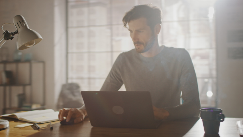 Professional Creative Man Sitting at His Desk in Home Office Studio Working on a Laptop, Concentrated Man Using Notebook Computer. Energetic Fast Paced Movement. 360 Degree Tracking Arc Shot Royalty-Free Stock Footage #1032113624