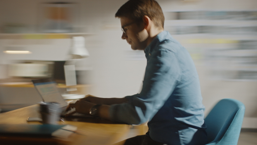Professional Creative Man Sitting at His Desk in Home Office Studio Working on a Laptop Writes down Notes. Energetic Fast Paced Time-Lapse Fast forward Movement. 360 Degree Tracking Arc Shot Royalty-Free Stock Footage #1032113660