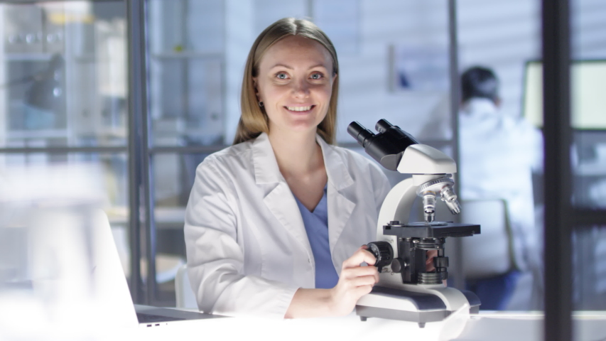 Waist-up portrait shot of female Caucasian research scientist working in busy lab, with unrecognizable colleagues in background, peering into microscope, then noticing camera and smiling warmly