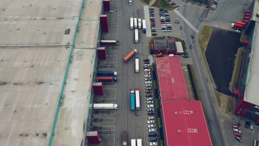 Aerial Shot of Industrial Warehouse Loading Dock where Many Truck with Semi Trailers Load Merchandise. #1032132320