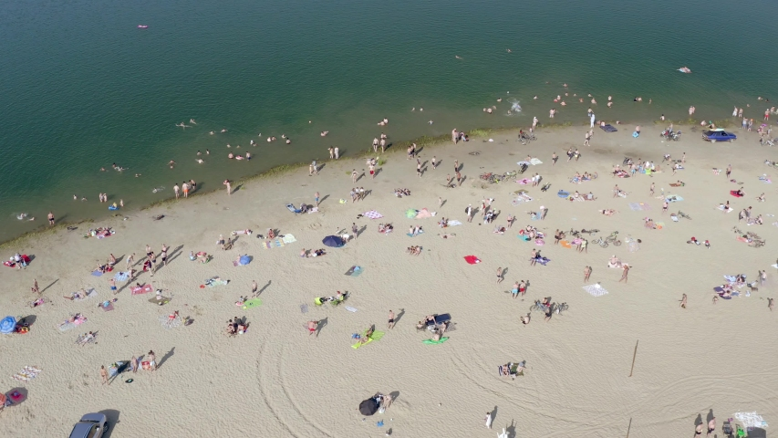 Domodedovo, Russia - June 07, 2019. Top view of sandy beach filled with people in summer. People relax and sunbathe on hot sunny day near pond. | Shutterstock HD Video #1032136379