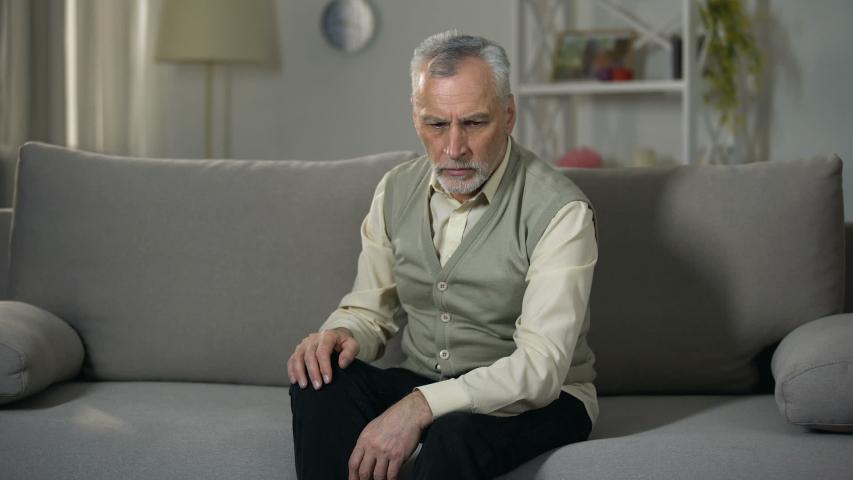 Old man rubbing knee, suffering joint pain, senior arthritis, osteoporosis