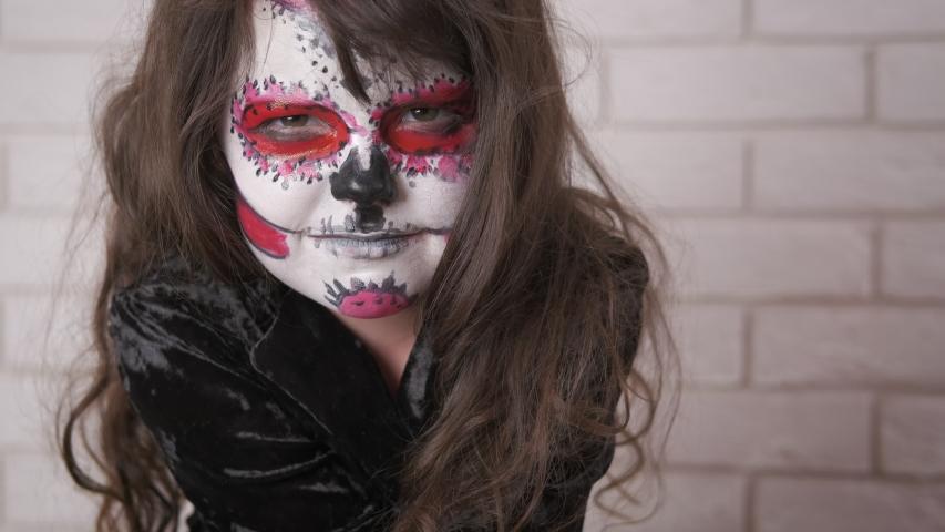 Halloween child. Portrait of an evil little girl with face art   Shutterstock HD Video #1032165737