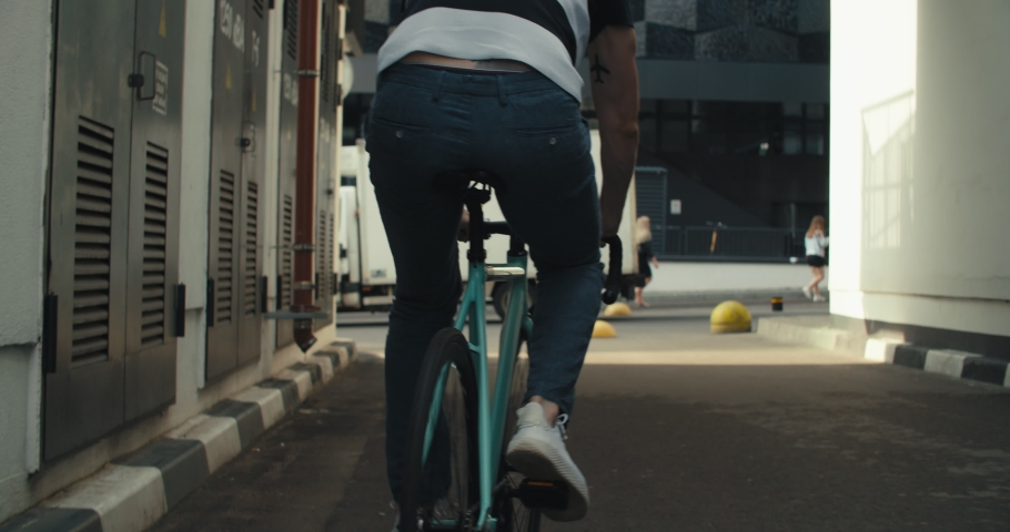 Young hipster man in casual summer cloths riding his fixed gear bike along the bike lane on city street. Front tracking shot young guy biking bicycle on road. 4K slow motion raw video footage 60 fps #1032171590