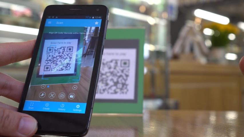 QR code cashless payment. Scan to pay system. Business or technology concept : young man using smartphone for scanning QR code for paying in the cafeteria