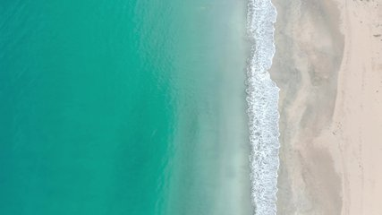 Tropical beach top view, waves break on tropical white sand beach top view. Caribbean sea waves seamless loop on amazing white sand beach. Video above turquoise blue sea water on the white sand shore.