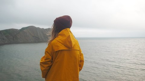 Back view of young woman hiker exploring nature in a dark misty rainy landscape. Mountains on the sea shore. Hiker girl wearing yellow raincoat trekking in cold stormy weather, hair blowing in wind.