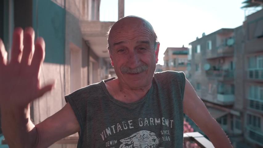 26.05.2019: Izmir/Turkey: Happy elderly man waving hand on balcony with superb sun flare. Retired old man in home, fun, happiness.