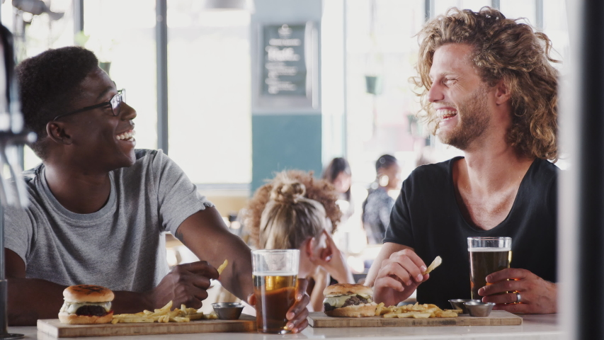 Two Male Friends Eating Food And Drinking Beer In Sports Bar #1032199838