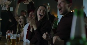 Group of male and female friends fans celebrating whilst watching game on TV screen in sports bar. 4K UHD RAW graded footage