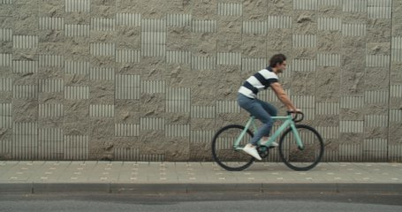 Cyclist guy riding fixed gear sport bike in sunny day on city. Hipster man in casual summer cloths and bicycle on street. Front tracking close-up of wheels. 4K slow motion raw video footage 60 fps
