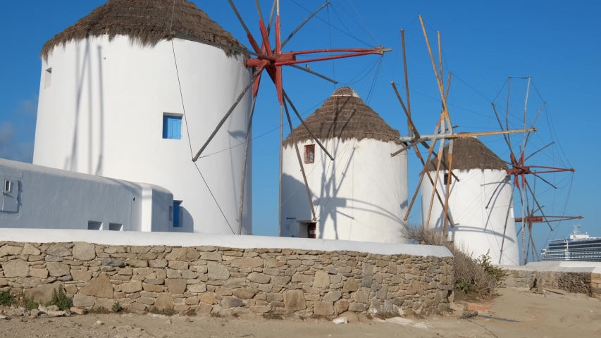 Scenic view of famous Mykonos town windmills. Traditional greek windmills on Mykonos island at sunrise with cruise ship in background, Cyclades, Greece. Walking with steadycam.   Shutterstock HD Video #1032220238