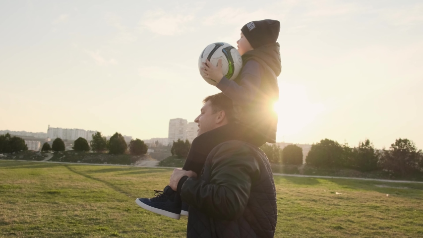 Father runs down the football fiels with his small son on the shoulders and has fun with him slow motion   Shutterstock HD Video #1032221099